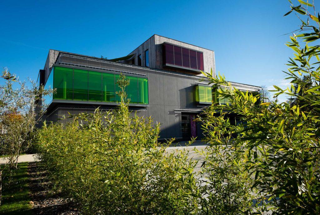 bâtiment moderne, Soëlys, vitres teintées, jaunes, vertes, arbres, ciel bleu