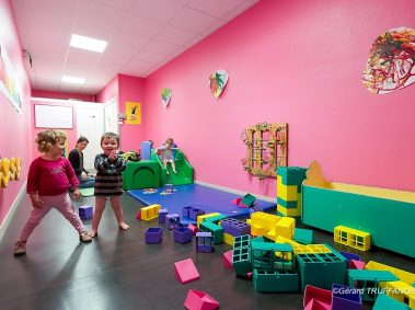 Crèche multi accueil les petits loups, salle avec peinture rose, des jouets, deux petites filles