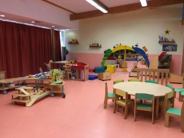 Salle d'activité du Relais Assistantes Maternelles, sol rose, petite table et chaises pour enfants, jouets,