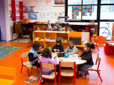 école maternelle, enfants assis autour d'une table en train de faire du collage