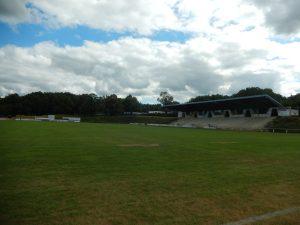 stade Bernard Delage, ciel nuageux, gazon bien vert, tribunes au loin