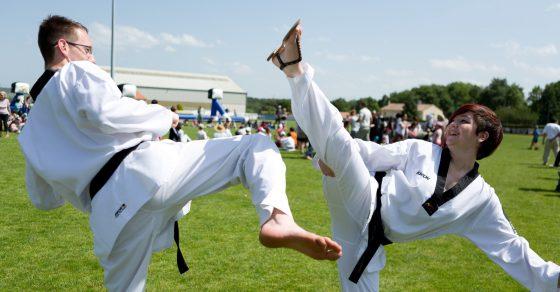 self-défense, fille contre garçon habillés d'un kimono blanc et d'une ceinture noire, en pleine action,