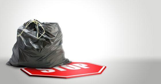sac poubelle plastique et panneau stop sur un fond bleu