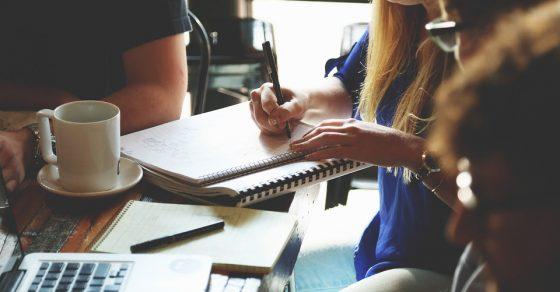 femmes et hommes en train de travailler autour d'un café